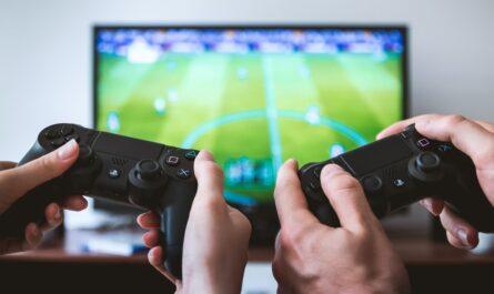 Dva hráči hrají FIFA, hru od Electronic Arts.